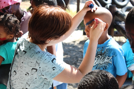 A Common Good volunteer lends her hand to face painting