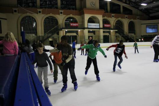 Learning how to skate on ice with the help of friends