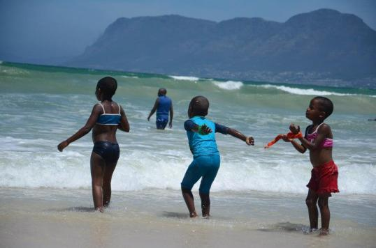 Enjoying the thrills of chilly waves at an Izandla Zethemba beach day